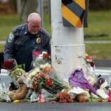 A police officer relocates items from a memorial to shooting victims that had been left in the middle of a busy intersection, Sunday, Dec. 16, 2012 in Newtown, Conn.  A gunman walked into Sandy Hook Elementary School in Newtown Friday and opened fire, killing 26 people, including 20 children.  The items were taken to nearby Saint Rose of Lima Roman Catholic Church. (AP Photo/Jason DeCrow)