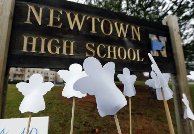 Angel cut-outs are displayed outside Newtown High School in Newtown, Conn., Sunday, Dec. 16, 2012. A gunman opened fire at Sandy Hook Elementary School in the town, killing 26 people, including 20 children before killing himself on Friday. (AP Photo/Charles Krupa) Photo: Charles Krupa, Associated Press / Associated Press