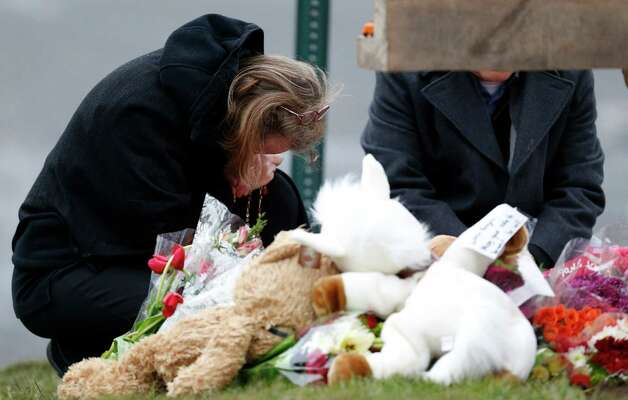 A woman pays her respects at a makeshift memorial outside St. Rose of Lima Roman Catholic Church before Mass, Sunday, Dec. 16, 2012, in Newtown, Conn. On Friday, a gunman allegedly killed his mother at their home and then opened fire inside the Sandy Hook Elementary School in Newtown, killing 26 people, including 20 children. (AP Photo/Julio Cortez) Photo: Julio Cortez, Associated Press / Associated Press