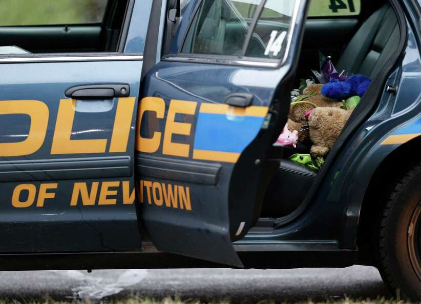 A teddy bear and flowers sit in the cruiser of Newtown Police Officer Maryhelen McCarthy while she p