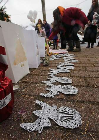 A woman lays flowers at the site of a makeshift memorial for school shooting victims at the village of Sandy Hook in Newtown, Conn., Sunday, Dec. 16, 2012. A gunman opened fire at Sandy Hook Elementary School in the town, killing 26 people, including 20 children before killing himself on Friday. (AP Photo/Charles Krupa) Photo: Charles Krupa, Associated Press