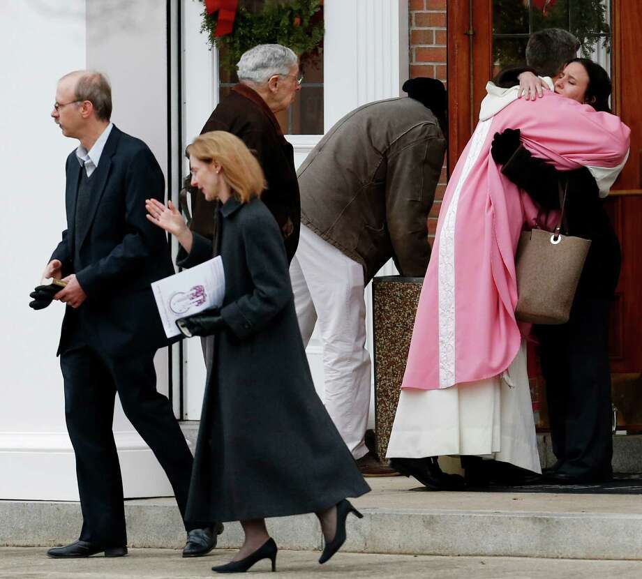 A priest embraces a woman outside St. Rose of Lima Roman Catholic Church between Masses, Sunday, Dec. 16, 2012, in Newtown, Conn. On Friday, a gunman allegedly killed his mother at their home and then opened fire inside the Sandy Hook Elementary School in Newtown, killing 26 people, including 20 children. (AP Photo/Julio Cortez) Photo: Julio Cortez, Associated Press / Associated Press
