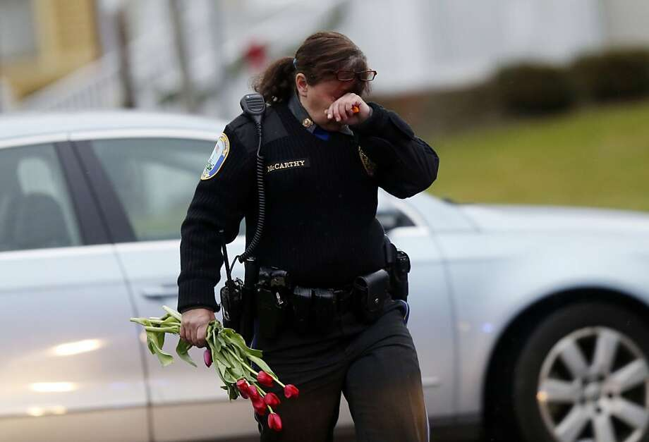 Newtown Police Officer Maryhelen McCarthy carries flowers near a memorial for shooting victims Sunday, Dec. 16, 2012 in Newtown, Conn.  A gunman walked into Sandy Hook Elementary School in Newtown, Friday and opened fire, killing 26 people, including 20 children. The flowers and other items were taken to nearby Saint Rose of Lima Roman Catholic Church. (AP Photo/Jason DeCrow) Photo: Jason DeCrow, Associated Press