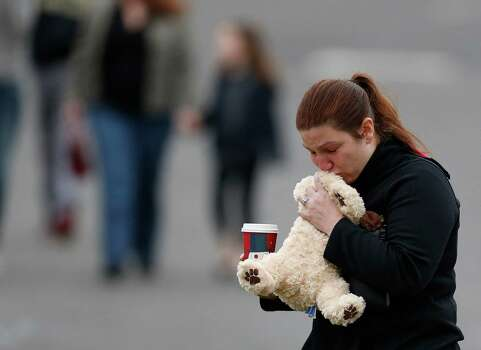 A woman kisses a stuffed animal before placing it on a makeshift memorial outside St. Rose of Lima Roman Catholic Church before Mass, Sunday, Dec. 16, 2012, in Newtown, Conn. On Friday, a gunman allegedly killed his mother at their home and then opened fire inside the Sandy Hook Elementary School, killing 26 people, including 20 children. (AP Photo/Julio Cortez) Photo: Julio Cortez, Associated Press / Associated Press