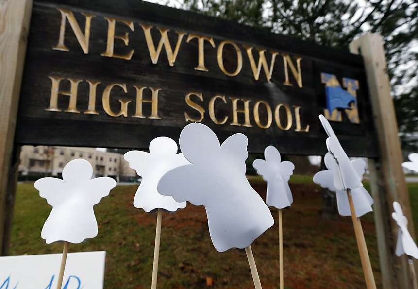 Angel cut-outs are displayed outside Newtown High School in Newtown, Conn., Sunday, Dec. 16, 2012. A