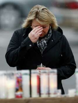 A woman blesses herself at a makeshift memorial outside of St. Rose of Lima Roman Catholic Church before Mass, Sunday, Dec. 16, 2012, in Newtown, Conn. On Friday, a gunman allegedly killed his mother at their home and then opened fire inside the Sandy Hook Elementary School, killing 26 people, including 20 children. (AP Photo/Julio Cortez) Photo: Julio Cortez, Associated Press / Associated Press