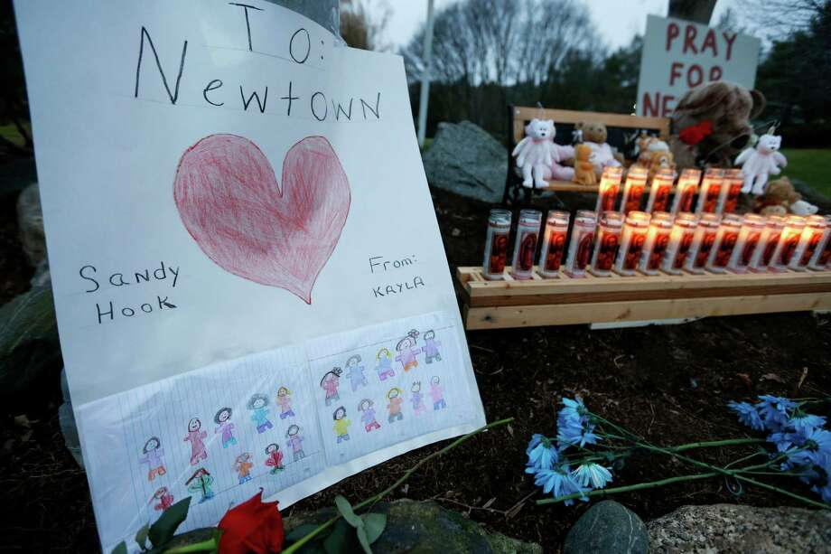 A child's message rests with a memorial for shooting victims, Sunday, Dec. 16, 2012, in Newtown, Conn. A gunman walked into Sandy Hook Elementary School in Newtown on Friday and opened fire, killing 26 people, including 20 children. (AP Photo/Jason DeCrow) Photo: Jason DeCrow, Associated Press / Associated Press