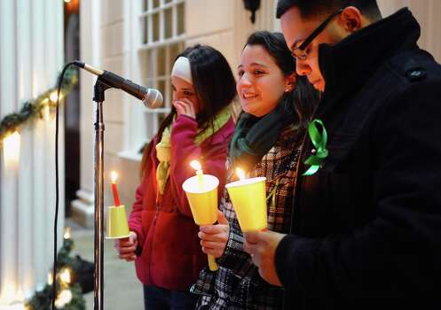 Jillian Soto, center, thanks the hundreds of people who came out to attend a candlelight vigil in memory of victims from the  mass shooting in Newtown, Conn., which was held behind Stratford High School on the Town Hall Green in Stratford, Conn. on Saturday December 15, 2012. Jillian's sister Vicki, a Stratford native, was a teacher at Sandy Hook Elementary School and was one of the victims in the shooting. At left is sister Carly Soto and family friend Louis Sanchez. (AP Photo/The Connecticut Post, Christian Abraham) MANDATORY CREDIT Photo: Christian Abraham, Associated Press / Associated Press