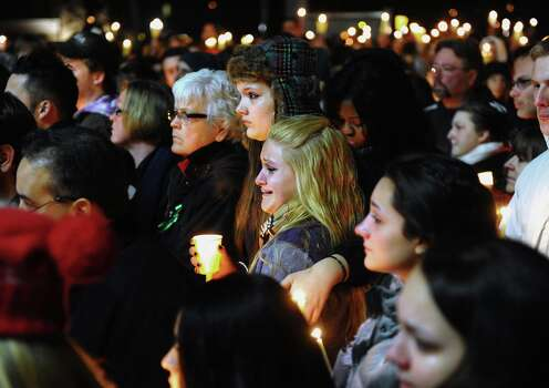 Stratford High School seniors Ally Kutzer and Caitlyn Larocque, center front, attend a candlelight vigil with hundreds of other in memory of victims from the mass shooting in Newtown, Saturday, Dec. 15, 2012 on the Town Hall Green in Stratford, Conn. (AP Photo/The Connecticut Post, Christian Abraham) MANDATORY CREDIT Photo: Christian Abraham, Associated Press / Associated Press