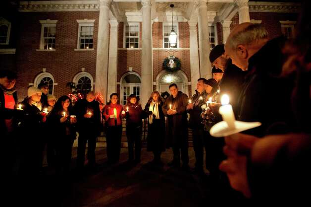 Mourners gather for a candlelight vigil outside the Edmond Town Hall, Saturday, Dec. 15, 2012, in Newtown, Conn.  A gunman walked into Sandy Hook Elementary School in Newtown Friday and opened fire, killing 26 people, including 20 children. (AP Photo/David Goldman) Photo: David Goldman, Associated Press / Associated Press