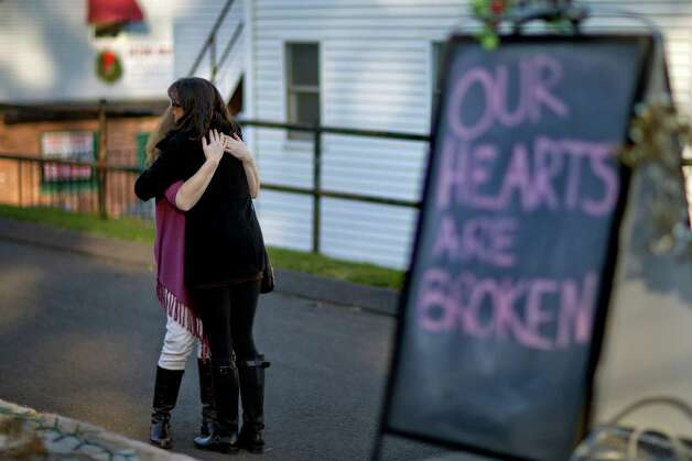 Shop owners Tamara Doherty, left, embraces Jackie Gaudet, right, as they meet outside their stores for the first time since being neighbors, just down the road from Sandy Hook Elementary School, Saturday, Dec. 15, 2012, in Newtown, Conn. The massacre of 26 children and adults at Sandy Hook Elementary school elicited horror and soul-searching around the world even as it raised more basic questions about why the gunman, 20-year-old Adam Lanza, would have been driven to such a crime and how he chose his victims. (AP Photo/David Goldman) Photo: David Goldman, Associated Press / Associated Press