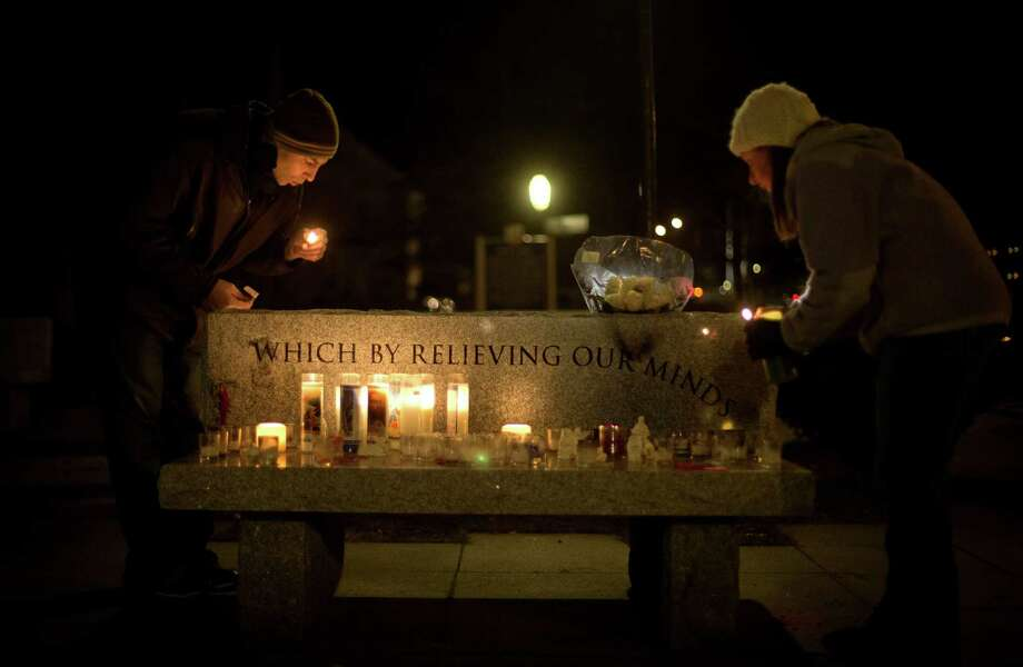 Brian Tenenhaus, left, blows out a match after lighting a candle at a vigil outside the Edmond Town Hall with Lauren Foster, right, Saturday, Dec. 15, 2012, in Newtown, Conn. A gunman walked into Sandy Hook Elementary School in Newtown Friday and opened fire, killing 26 people, including 20 children. (AP Photo/David Goldman) Photo: David Goldman, Associated Press / Associated Press