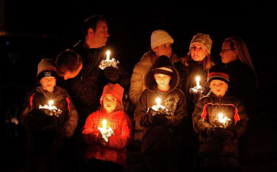 Mourners gather for a candlelight vigil at Ram's Pasture to remember shooting victims, Saturday, Dec