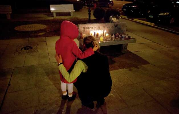 Rhonda Eleish, right, embraces her daughter Kari Ergmann, 6, both of Bridgewater, Conn., next to a candlelight vigil outside the Edmond Town Hall, Saturday, Dec. 15, 2012, in Newtown, Conn. Eleish suspects her daughter knew one of the victims of Friday's shooting at Sandy Hook Elementary School in Newtown that killed 26 people, including 20 children. (AP Photo/David Goldman) Photo: David Goldman, Associated Press / Associated Press