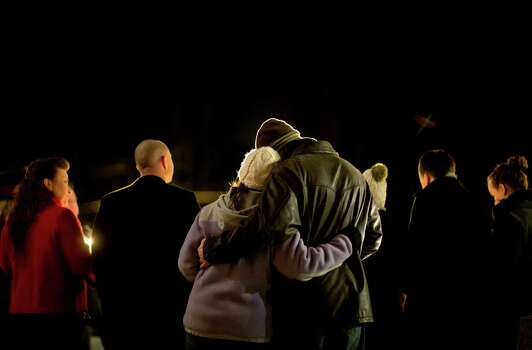 Brian Tenenhaus, right, comforts Lauren Foster, during a candlelight vigil outside the Edmond Town Hall, Saturday, Dec. 15, 2012, in Newtown, Conn.  A gunman walked into Sandy Hook Elementary School in Newtown Friday and opened fire, killing 26 people, including 20 children. (AP Photo/David Goldman) Photo: David Goldman, Associated Press / Associated Press