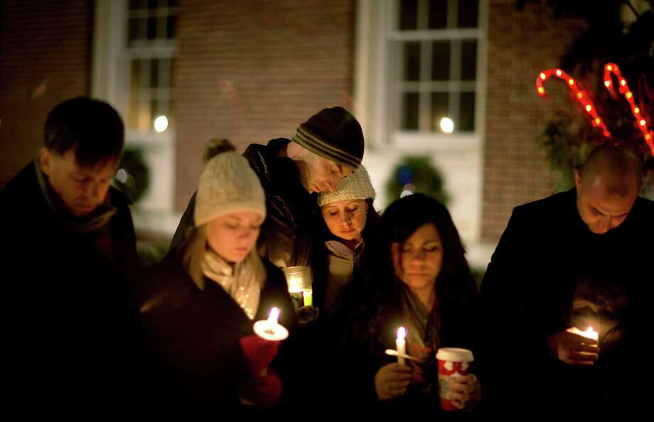 Brian Tenenhaus, center left, comforts Lauren Foster, during a candlelight vigil outside the Edmond Town Hall, Saturday, Dec. 15, 2012, in Newtown, Conn.  A gunman walked into Sandy Hook Elementary School in Newtown Friday and opened fire, killing 26 people, including 20 children. (AP Photo/David Goldman) Photo: David Goldman, Associated Press / Associated Press