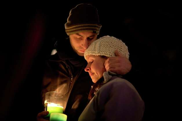 Brian Tenenhaus, left, comforts Lauren Foster, during a candlelight vigil outside the Edmond Town Hall, Saturday, Dec. 15, 2012, in Newtown, Conn.  A gunman walked into Sandy Hook Elementary School in Newtown Friday and opened fire, killing 26 people, including 20 children. (AP Photo/David Goldman) Photo: David Goldman, Associated Press / Associated Press