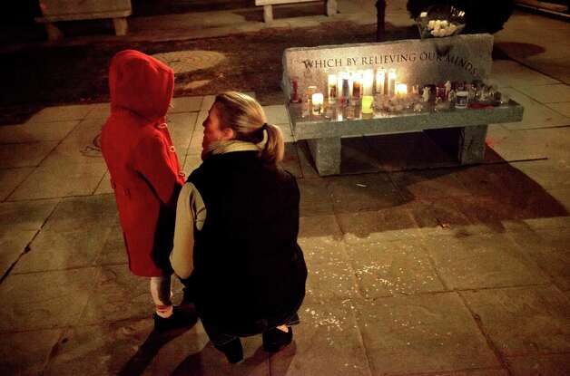 Rhonda Eleish, right, talks to her daughter Kari Ergmann, 6, both of Bridgewater, Conn., next to a candlelight vigil outside the Edmond Town Hall, Saturday, Dec. 15, 2012, in Newtown, Conn. Eleish suspects her daughter knew one of the victims of Friday's shooting at Sandy Hook Elementary School in Newtown that killed 26 people, including 20 children. (AP Photo/David Goldman) Photo: David Goldman, Associated Press / Associated Press