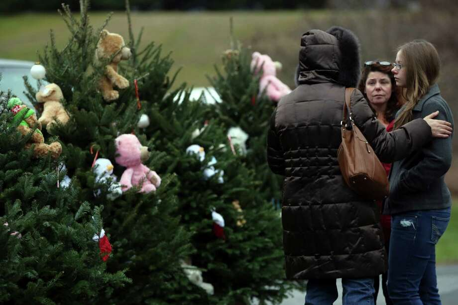 Mourners grieve at one of the makeshift memorials for the victims of the Sandy Hook Elementary School shooting, Sunday, Dec. 16, 2012 in Newtown, Conn. On Friday, a gunman allegedly killed his mother at their home and then opened fire inside the school, killing 26 people, including 20 children. (AP Photo/Mary Altaffer) Photo: Mary Altaffer, Associated Press / Associated Press