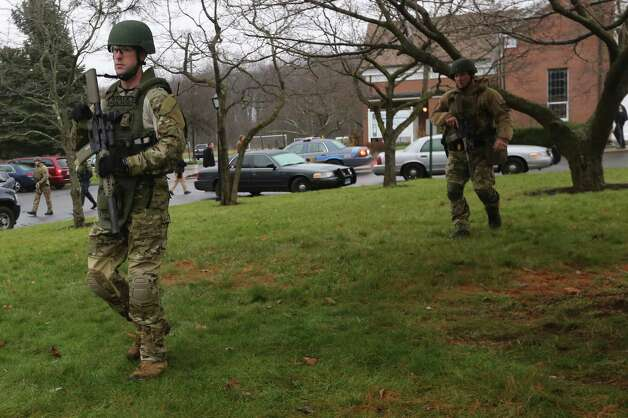 Connecticut State Police officers respond to a bomb threat outside of St. Rose of Lima Roman Catholic Church, Sunday, Dec. 16, 2012 in Newtown, Conn. Worshippers hurriedly left the church Sunday, not far from where a gunman opened fire Friday inside the Sandy Hook Elementary School in Newtown. Police later said nothing dangerous was found. (AP Photo/Mary Altaffer) Photo: Mary Altaffer, Associated Press / Associated Press
