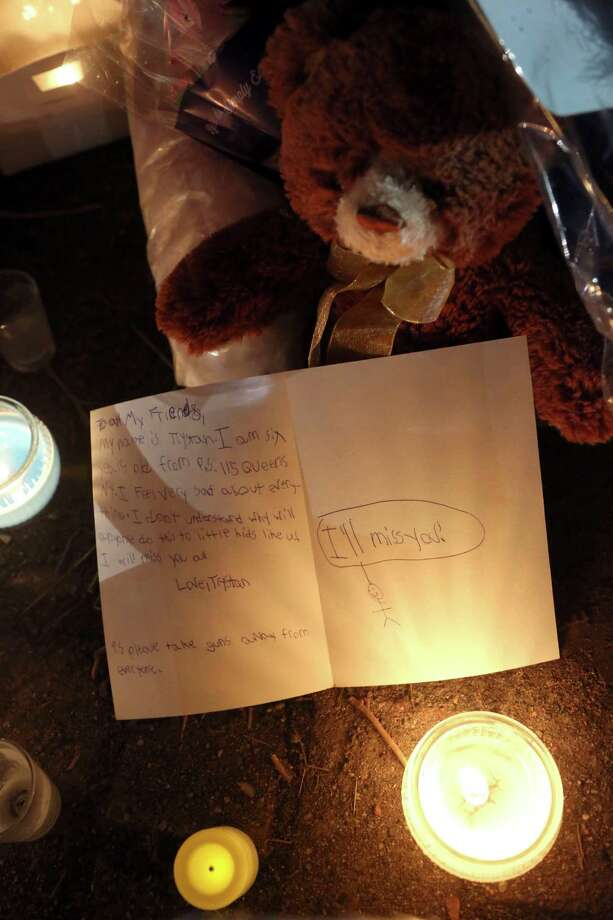 A personal note from a child is placed on a memorial for the victims of the Sandy Hook Elementary School shooting, Sunday, Dec. 16, 2012, in Newtown, Conn. A gunman walked into the school Friday and opened fire, killing 26 people, including 20 children. (AP Photo/Mary Altaffer) Photo: Mary Altaffer, Associated Press / Associated Press