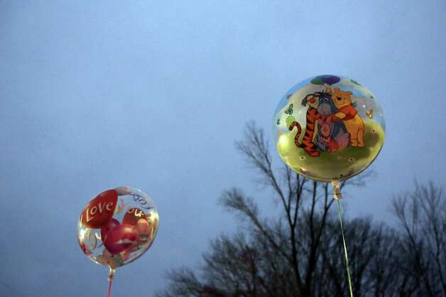 Balloons fly from a memorial for the victims of the Sandy Hook Elementary School shooting, Sunday, Dec. 16, 2012, in the Sandy Hook village of Newtown, Conn. A gunman walked into the school Friday and opened fire, killing 26 people, including 20 children. (AP Photo/Mary Altaffer) Photo: Mary Altaffer, Associated Press / Associated Press