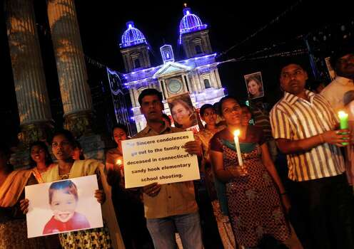 Indians carry placards and photographs of Connecticut shooting victims as they participate in a candlelight vigil outside a Catholic church in Bangalore, India, Sunday, Dec. 16, 2012. A gunman walked into Sandy Hook Elementary School in Newtown, Connecticut Friday and opened fire, killing 26 people, including 20 children. (AP Photo/Aijaz Rahi) Photo: Aijaz Rahi, Associated Press / Associated Press