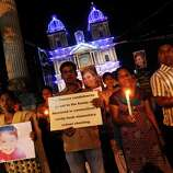 Indians carry placards and photographs of Connecticut shooting victims as they participate in a candlelight vigil outside a Catholic church in Bangalore, India, Sunday, Dec. 16, 2012. A gunman walked into Sandy Hook Elementary School in Newtown, Connecticut Friday and opened fire, killing 26 people, including 20 children. (AP Photo/Aijaz Rahi)