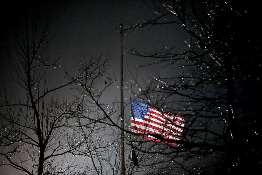 A U.S. flag flies at half staff outside the  Newtown High School before President Barack Obama is sc