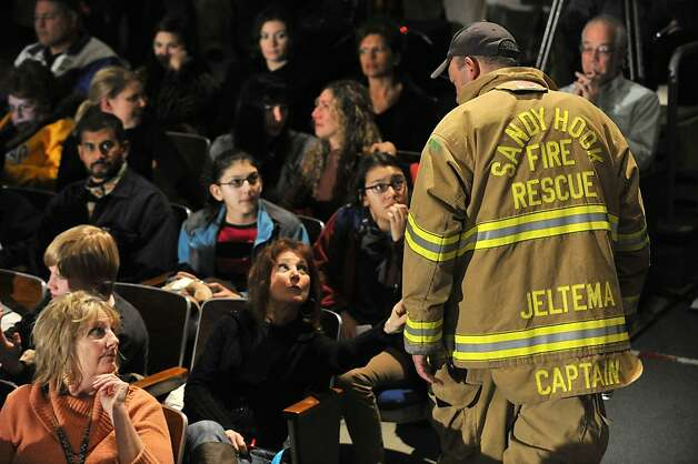 A Sandy Hook firefighter talks to people waiting for President Barack Obama to speak in the Newtown High School auditorium on Sunday, Dec. 16, 2012. Photo: Jason Rearick