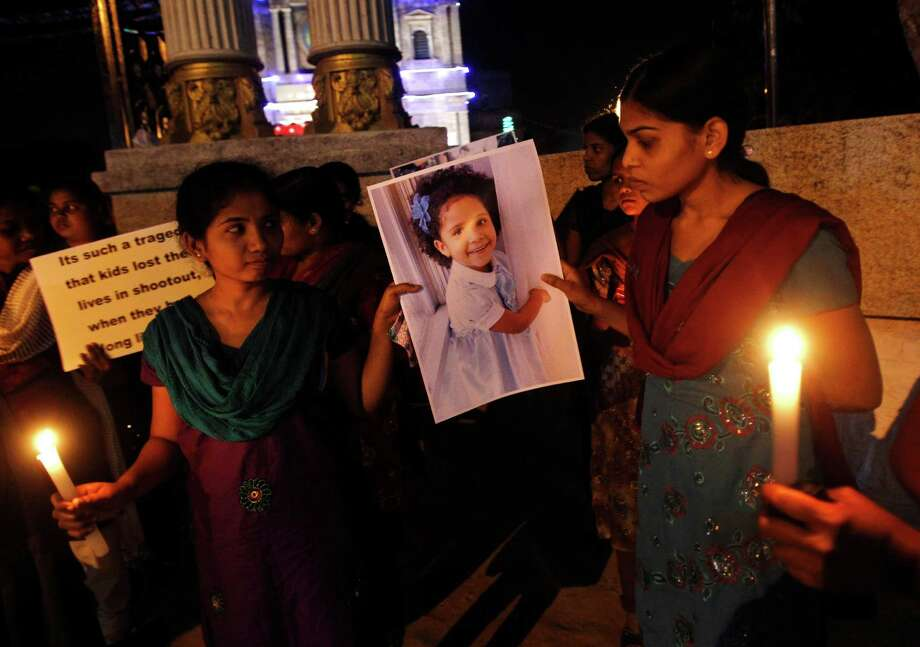 Indian women carry a photograph of a Connecticut shooting victim as they participate in a candlelight vigil outside a Catholic church in Bangalore, India, Sunday, Dec. 16, 2012. A gunman walked into Sandy Hook Elementary School in Newtown, Connecticut Friday and opened fire, killing 26 people, including 20 children. (AP Photo/Aijaz Rahi) Photo: Aijaz Rahi, Associated Press / Associated Press