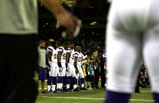 Members of the Minnesota Vikings hold hands during a moment of silence in honor of those killed Friday in shooting rampage at Sandy Hook Elementary School in Newtown, Conn., before the start of an NFL football game between the St. Louis Rams and the Minnesota Vikings Sunday, Dec. 16, 2012, in St. Louis.  A gunman walked into Sandy Hook Elementary School in Newtown, Conn. Friday and opened fire, killing 20 children and six adults.  (AP Photo/Jeff Roberson) Photo: Jeff Roberson, Associated Press / Associated Press