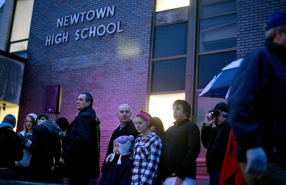 People wait in line to enter Newtown High School for a memorial vigil attended by President Barack O