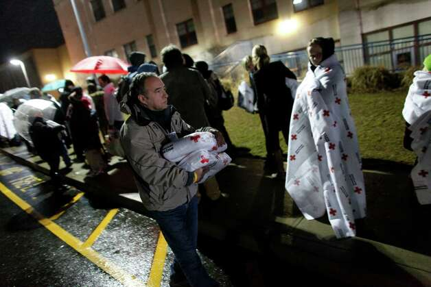Red Cross volunteer Michael Cianciolo distributes blankets to protect people from the cold, rainy weather as they wait in line to attend an interfaith vigil with President Barack Obama, Sunday, Dec. 16, 2012, in Newtown, Conn. A gunman walked into Sandy Hook Elementary School in Newtown Friday and opened fire, killing 26 people, including 20 children. (AP Photo/Jason DeCrow) Photo: AP