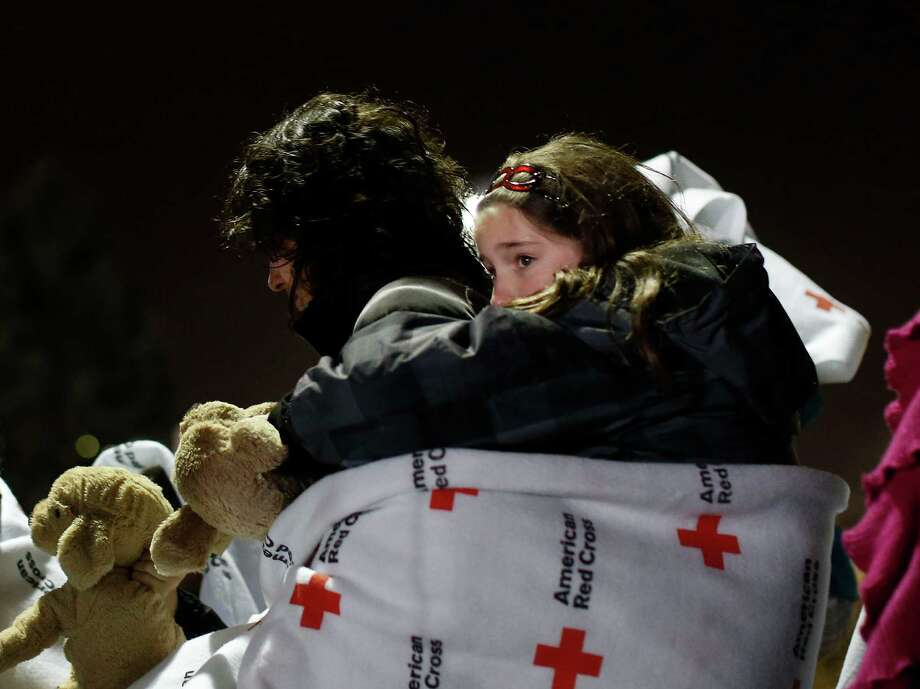 Eight-year old Shayne Frate, a third grade student at Sandy Hook Elementary School, hangs from her mother Valerie's back, wrapped in a Red Cross blanket to protect her from the cold, rainy weather, as she waits in line to attend an interfaith vigil with President Barack Obama, Sunday, Dec. 16, 2012, in Newtown, Conn. A gunman walked into Sandy Hook Elementary School in Newtown Friday and opened fire, killing 26 people, including 20 children. (AP Photo/Jason DeCrow) Photo: AP