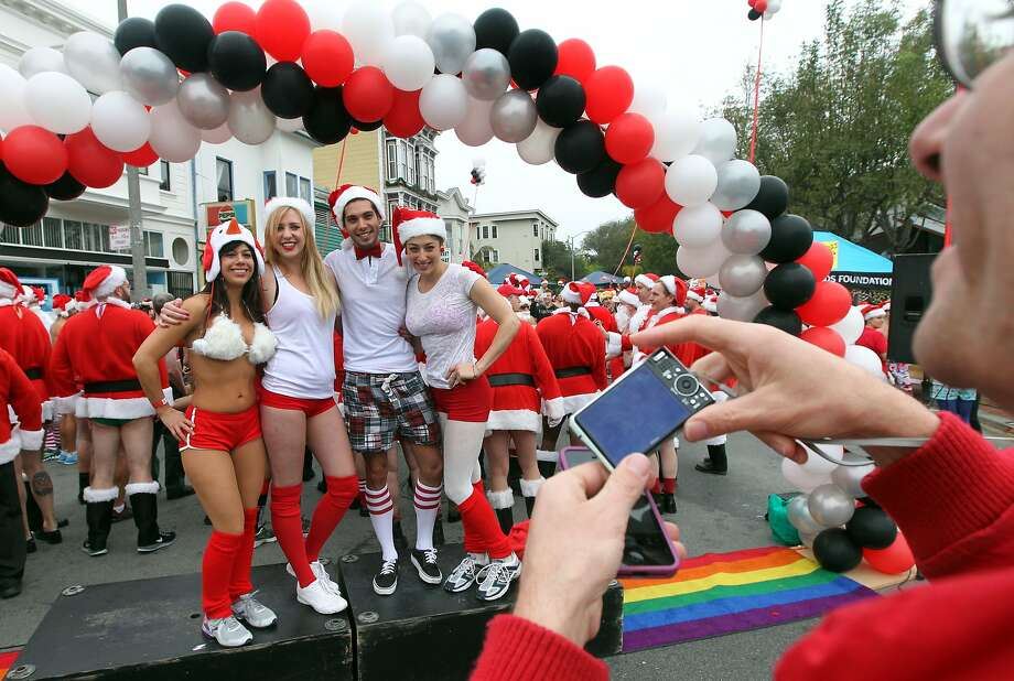 Runners pose for photos prior to the start of the annual Santa Skivvies Run Sunday, Dec. 16, 2012. Four hundred volunteers and joggers took part, raising $43,000 for the AIDS Foundation. Runners started at the Lookout Bar on Market Street then ran through the Castro District taking a spontaneous route, much to the delight of onlookers. Photo: Lance Iversen, The Chronicle