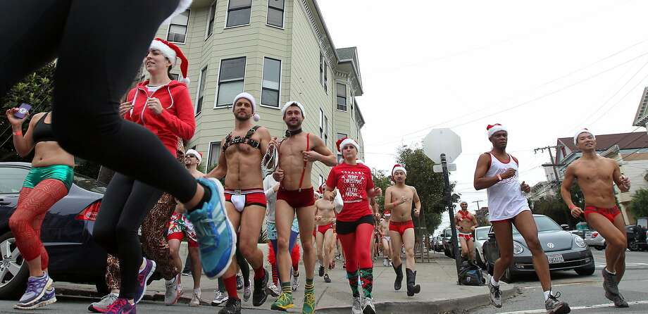 Runners make their way down Noe Street during the annual Santa Skivvies Run Sunday, Dec. 16, 2012. Four hundred volunteers and joggers took part, raising $43,000 for the AIDS Foundation. Runners started at the Lookout Bar on Market Street then ran through the Castro District taking a spontaneous route, much to the delight of onlookers. Photo: Lance Iversen, The Chronicle