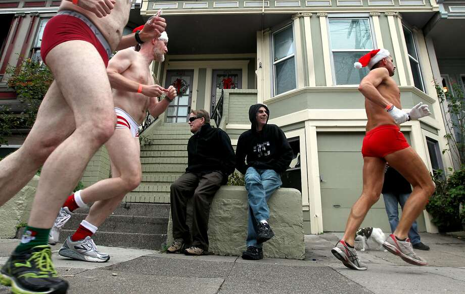Cameron Dean, left, and Dennis Smith watch runners make their way down 18th Street during the annual Santa Skivvies Run Sunday, Dec. 16, 2012. Four hundred volunteers and joggers took part, raising $43,000 for the AIDS Foundation. Runners started at the Lookout Bar on Market Street then ran through the Castro District taking a spontaneous route, much to the delight of onlookers. Photo: Lance Iversen, The Chronicle
