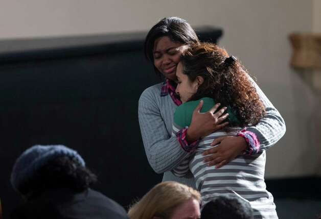 Residents greet each other before the start of an interfaith vigil for the victims of the Sandy Hook Elementary School shooting on Sunday, Dec. 16, 2012, at Newtown High School in Newtown, Conn. A gunman walked into the school Friday and opened fire, killing 26 people, including 20 children. President Barack Obama is to scheduled to speak at the event.  (AP Photo/ Evan Vucci) Photo: AP