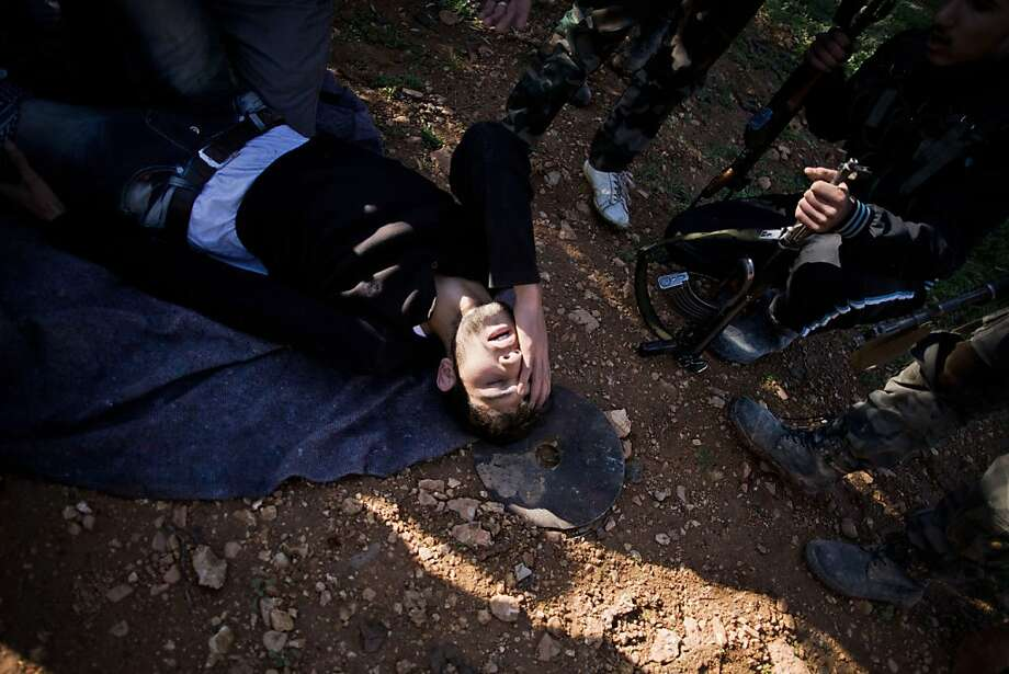 A free Syrian Army fighter lies on the ground after been hit by a Syrian Army sniper during the assault on a military base in Tal Sheen, Syria, Saturday, Dec 15, 2012 (AP Photo / Manu Brabo) Photo: Manu Brabo, Associated Press