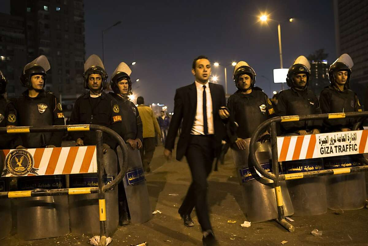 CAIRO, EGYPT - DECEMBER 16: An Egyptian man walks past riot police as they stand guard in front of Dokki police station on December 16, 2012 in Cairo, Egypt. Egyptian police were on high alert after news of a planned protest by Salafist supporters of Hazem Abu Ismail, after an attack on WAFD party headquarters last night on election day. The protest was cancelled after an announcement on Hazem Abu Ismail's Facebook account. (Photo by Daniel Berehulak/Getty Images)