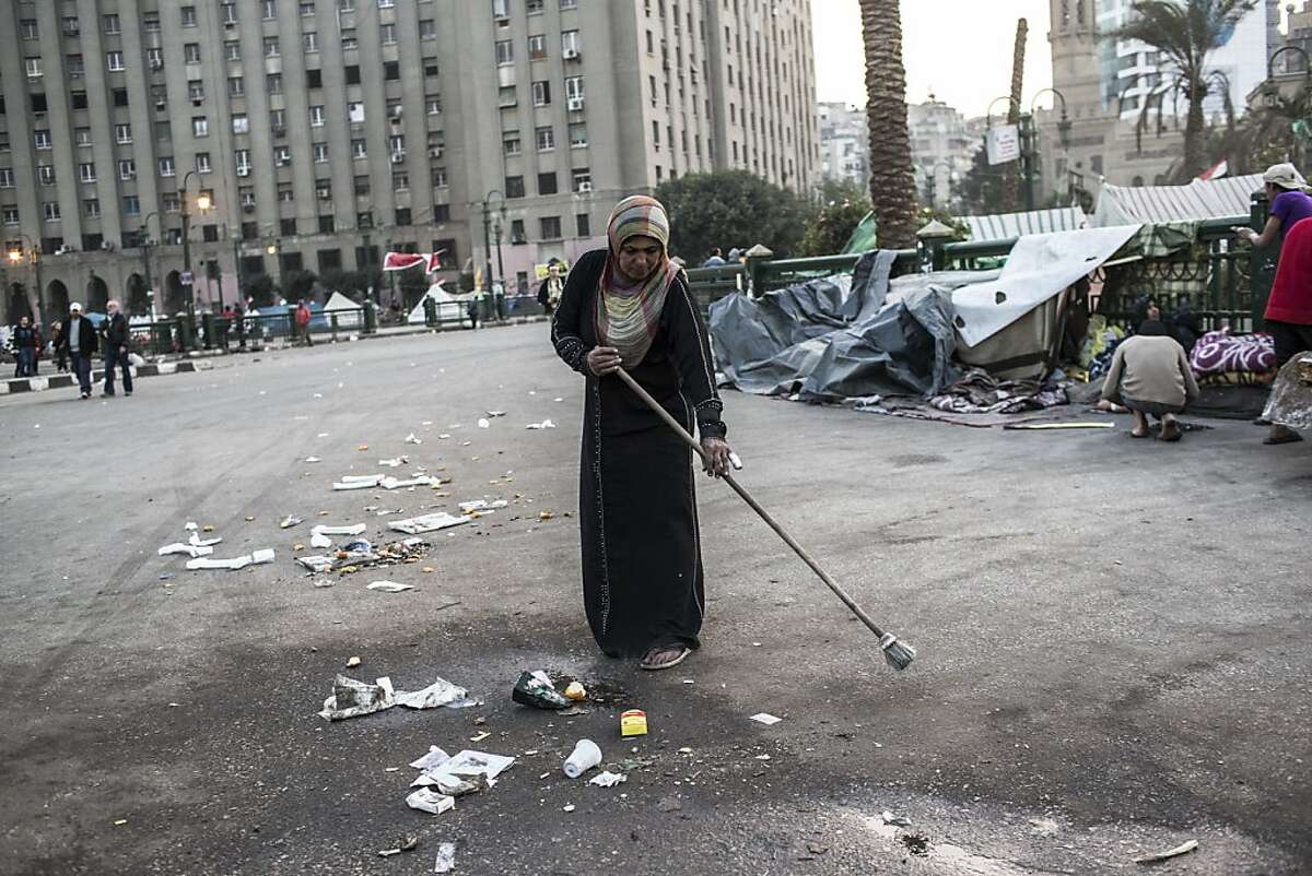 CAIRO, EGYPT - DECEMBER 16: An Egyptian woman sweeps the road in Tahrir Square on December 16, 2012 in Cairo, Egypt. Egyptians went to the polls yesterday to vote in a referendum on a proposed constitution that could change the character of Egypt and gradually bring its laws closer to Sharia, or Islamic law. The Freedom and Justice Party reported that semi-official results, based on 99.2 percent of polling stations, show 56.5 percent of voters approving the constitution and 43.5 percent rejecting it. (Photo by Daniel Berehulak/Getty Images)