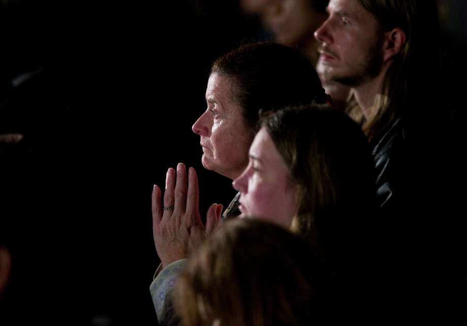 Residents look on during an interfaith vigil for the victims of the Sandy Hook Elementary School shooting on Sunday, Dec. 16, 2012, at Newtown High School in Newtown, Conn. A gunman walked into the elementary school Friday and opened fire, killing 26 people, including 20 children. President Barack Obama is schedule to speak during the vigil.  (AP Photo/ Evan Vucci) Photo: AP