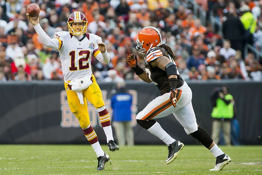 Redskins quarterback Kirk Cousins eludes Browns defensive end Jabaal Sheard. Photo: Jason Miller, Getty Images