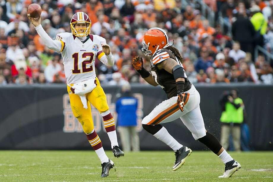 Redskins quarterback Kirk Cousins eludes Browns defensive end Jabaal Sheard. Photo: Jason Miller, Getty Images