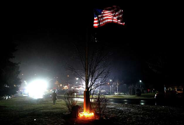 A young boy places a candle with others at the base of a flagpole outside Newtown High School before an interfaith vigil with President Barack Obama, Sunday, Dec. 16, 2012, in Newtown, Conn.  A gunman walked into Sandy Hook Elementary School in Newtown Friday and opened fire, killing 26 people, including 20 children. (AP Photo/Jason DeCrow) Photo: AP
