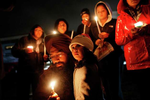 Eknoor Kaur, 3, stands with her father Guramril Singh during a candlelight vigil outside Newtown High School before an interfaith vigil with President Barack Obama, Sunday, Dec. 16, 2012, in Newtown, Conn.  A gunman walked into Sandy Hook Elementary School in Newtown Friday and opened fire, killing 26 people, including 20 children. (AP Photo/Jason DeCrow) Photo: AP