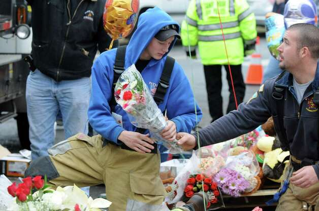 Firefighters rearranged flowers and teddy bears left by mourners outside Sandy Hook Elementary School in Newtown, Conn on Sunday Dec. 16, 2012. Photo: Will Waldron, Hearst Newspapers/Will Waldron / The News-Times