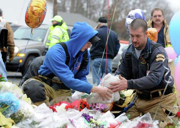 Firefighters rearranged flowers and teddy bears left by mourners outside Sandy Hook Elementary School, in Newtown, Conn. on Sunday Dec. 16, 2012. Photo: Will Waldron, Hearst Newspapers/Will Waldron / The News-Times