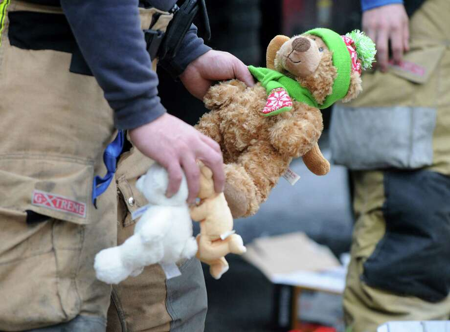Firefighters rearranged flowers and teddy bears which were left by mourners outside Sandy Hook Elementary School in Newtown, Conn. Sunday Dec. 16, 2012. Photo: Will Waldron, Hearst Newspapers/Will Waldron / The News-Times